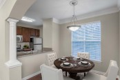 Dining area with pendant lighting crown molding and wood look flooring