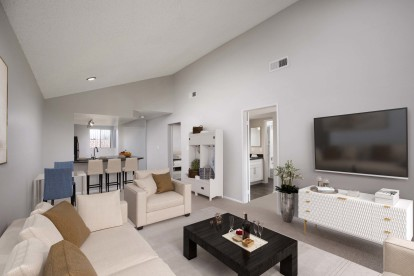 Living and dining room with angled ceiling carpet flooring and track lighting in kitchen