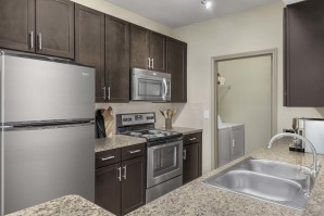 Kitchen with stainless steel appliances next to laundry room with full size washer and dryer