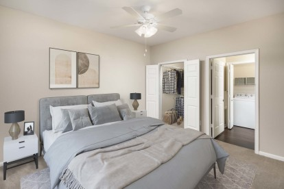 Bedroom with carpet and attached closet and bathroom with laundry area