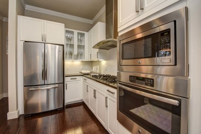 The townhomes kitchen with gas cooktops, stainless steel appliances, and wood flooring