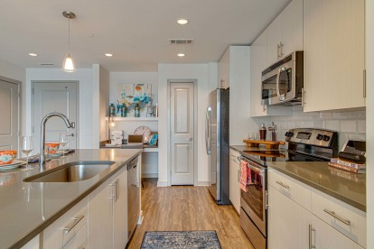 Kitchen with light wood cabinets, gray countertops and stainless steel appliances