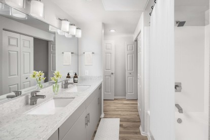 Contemporary bathroom with dual vanity white quartz countertop, gray cabinets, curved shower rod, and wood-like flooring