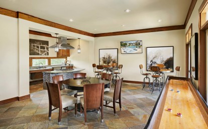 Game lounge and kitchen with seating and shuffleboard table