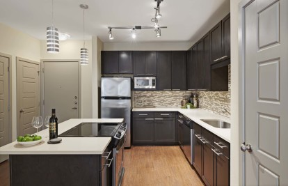 Kitchen with granite countertops stainless steel appliances glass cooktop and wood look flooring