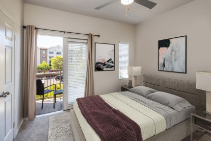 Townhome bedroom with ceiling fan and french doors to balcony