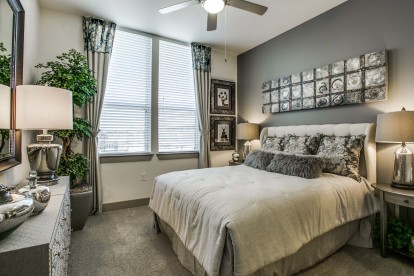 Bedroom with carpet flooring ceiling fan and accent wall