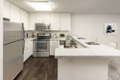 Open concept kitchen stainless steel appliances barstool seating