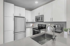 Kitchen with gray quartz countertops and white cabinets