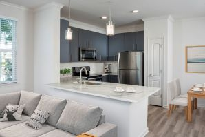 Gorgeous open kitchen with gray cabinetry, kitchen pantry, quartz countertops, undermount sink with gooseneck spray faucet, and pendant lighting