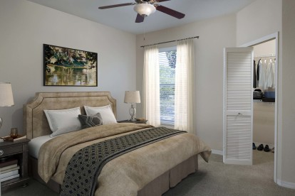 Bedroom with walk in closet and lighted ceiling fan