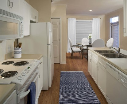 Neighborhood one kitchen with white appliances electric cooktop and wood look flooring