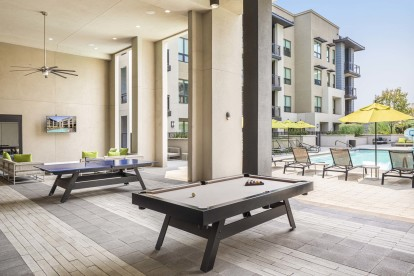 Covered poolside outdoor lounge with billiards ping pong and seating