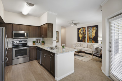 Contemporary-style kitchen and living room at Camden Farmers Market Apartments in Dallas, TX