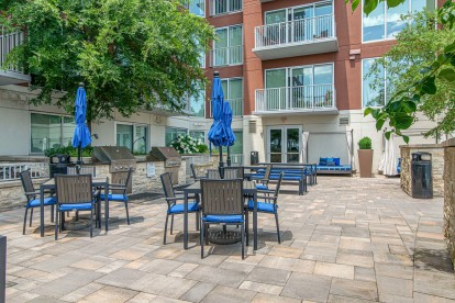 Grills and outdoor seating next to the pool