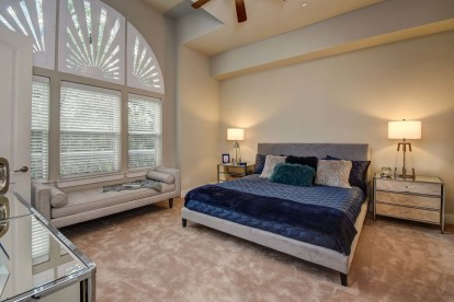 The townhomes bedroom with curved windows, angled ceiling, and ceiling fan