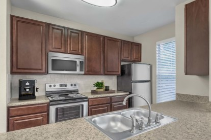 Kitchen with granite style countertops stainless steel appliances and tile backsplash