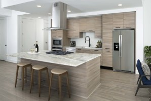 Warm modern finishes kitchen with quartz countertops stainless steel appliances and large kitchen islands