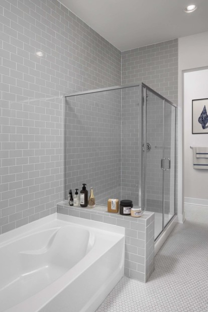 Penthouse bathroom with separate bathtub and glass enclosed shower with floor to ceiling tile