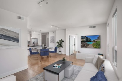 Open concept floor plan living and dining area with wood look flooring