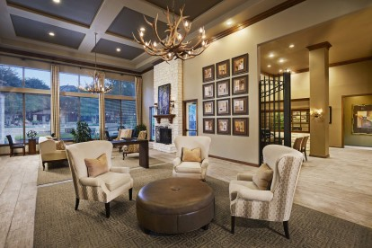 Resident lounge with fireplace and comfortable seating alongside pool