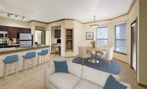 Living and dining room with built in desk and bookshelf carpet flooring and pendant lighting