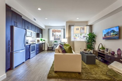 Open concept studio living and dining area with kitchen featuring stainless steel appliances and wood style flooring