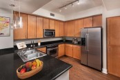 Kitchen with black granite countertops and stainless steel appliances