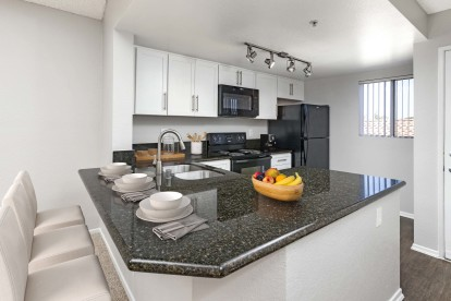 Kitchen with window and bar seating granite countertops and black appliances
