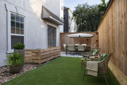 The townhomes private side yard with turf, dining, and seating areas