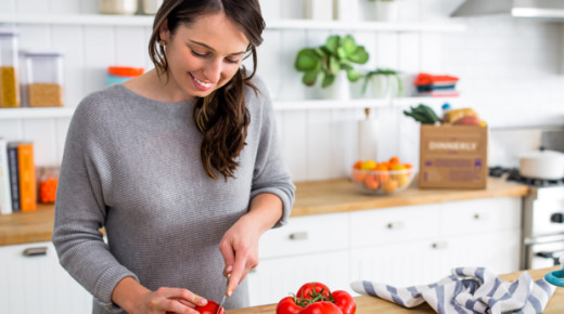 Woman cutting red tomatoes on a wooden chopping board