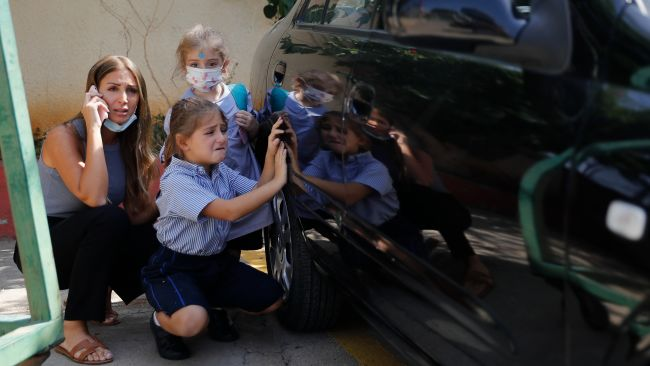 A Lebanese mother with her children hide behind a car from sniper fire outside a school, in the Christian neighborhood of Ain el-Remaneh.
