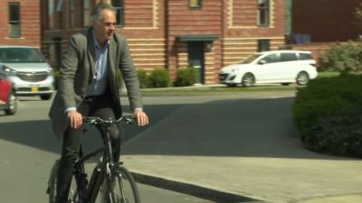 Green Party co-leader Jonathan Bartley riding an electric bicycle through a business park in bristol