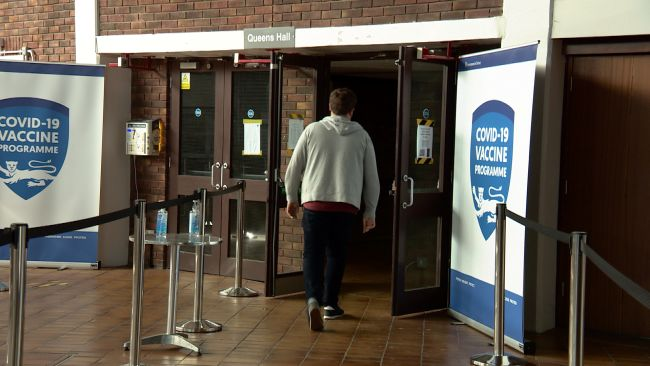 Young person walking into vaccine centre. Credit ITV Channel TV.