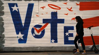 A woman walks past a voting sign painted on a wall Monday, November 2020, in the Venice Beach section of Los Angeles.