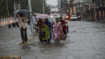 People make their way through a flooded street during monsoon rains Jammu, India.