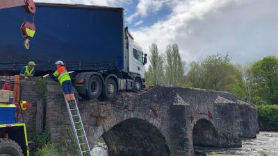 A lorry was left hanging off the edge of a Grade II listed stone bridge after colliding with it at 4am on Tuesday 18 May