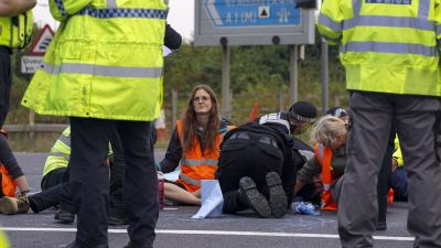 Police officers work to free protesters who had glued themselves to a slip road at Junction 4 of the A1(M), near Hatfield, where climate activists carried out a further action after demonstrations which took place last week across junctions in Kent, Essex, Hertfordshire and Surrey. Picture date: Monday September 20, 2021.  Steve Parsons/PA