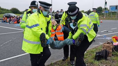 Police officers carry away a protester who had glued himself to the highway at a slip road at Junction 4 of the A1(M), near Hatfield, where climate activists carried out a further action after demonstrations which took place last week across junctions in Kent, Essex, Hertfordshire and Surrey. Picture date: Monday September 20, 2021. PA