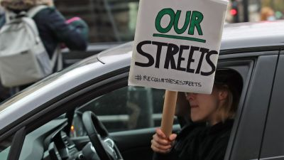 """A woman holding a Reclaim the Streets placard out of the passenger window drives past New Scotland Yard in London, the day after clashes between police and crowds who gathered on Clapham Common on Saturday night to remember Sarah Everard. The Metropolitan Police has faced intense criticism for its handling of the vigil, with officers accused of """"grabbing and manhandling"""" women during clashes with the crowd. Picture date: Sunday March 14, 2021."""