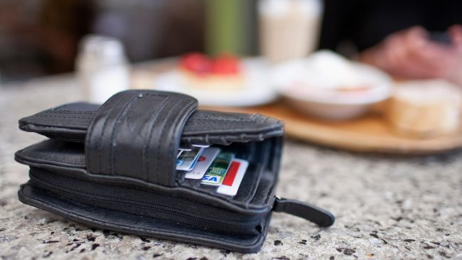 A wallet out on the table with some food in the background