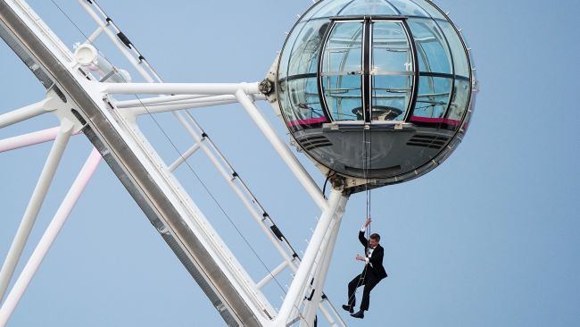 A man dressed as Britain's most famous secret service agent, James Bond, hangs from a pod on the lastminute.com London Eye, the landmark tourist attraction in central London, ahead of the world premiere of No Time To Die, the latest instalment in the Bond franchise. Picture date: Tuesday September 28, 2021.