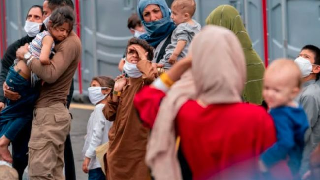 People evacuated from Afghanistan step off a bus as they arrive at a processing centre