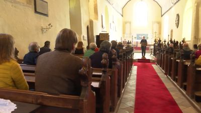 Campaigners sitting in church pews listening to someone talk from a lectern