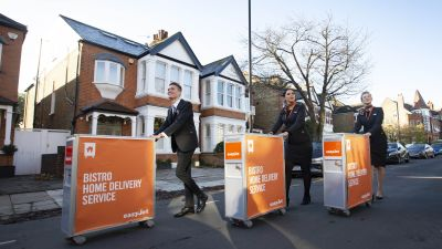 Cabin Crew (left to right) Matteo Lorenzini, Hanna Essemiani and Charlotte Kelson celebrate easyJet's 25th birthday, as the airline launches the world's first inflight trolley service at home, in partnership with Deliveroo on December 17, 2020.