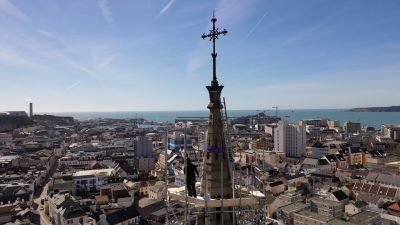 Drone shot of St Thomas' Church Spire with view of St Helier out to sea.