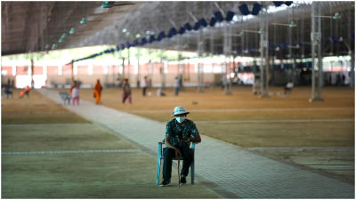 A volunteer keeps guard as workers prepare a facility that can accommodate more than ten thousand COVID-19 patients.