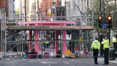 Workers remove part of a large pink strcture that had been used by environmental activists from Extinction Rebellion to block the junction of Long Acre and Upper St Martin's Lane in London.