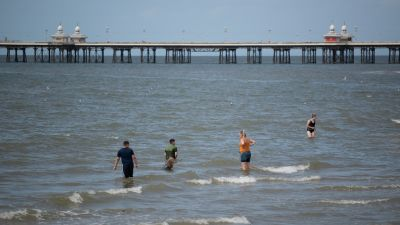 People enjoy the warm weather by participating in activities on Blackpool beach