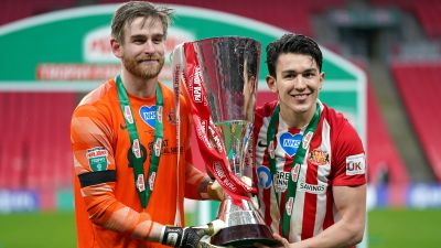 Sunderland goalkeeper Lee Burge (left) and Luke O'Nien celebrates with the Papa John's Trophy after the 2021 final at Wembley Stadium, London. Picture date: Sunday, March 14, 2021.